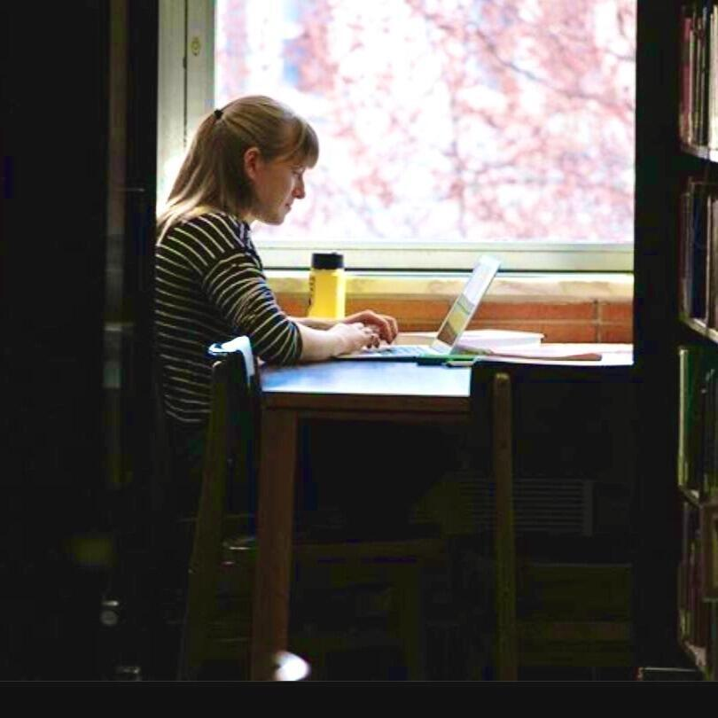 Student studying in the library in front of a window