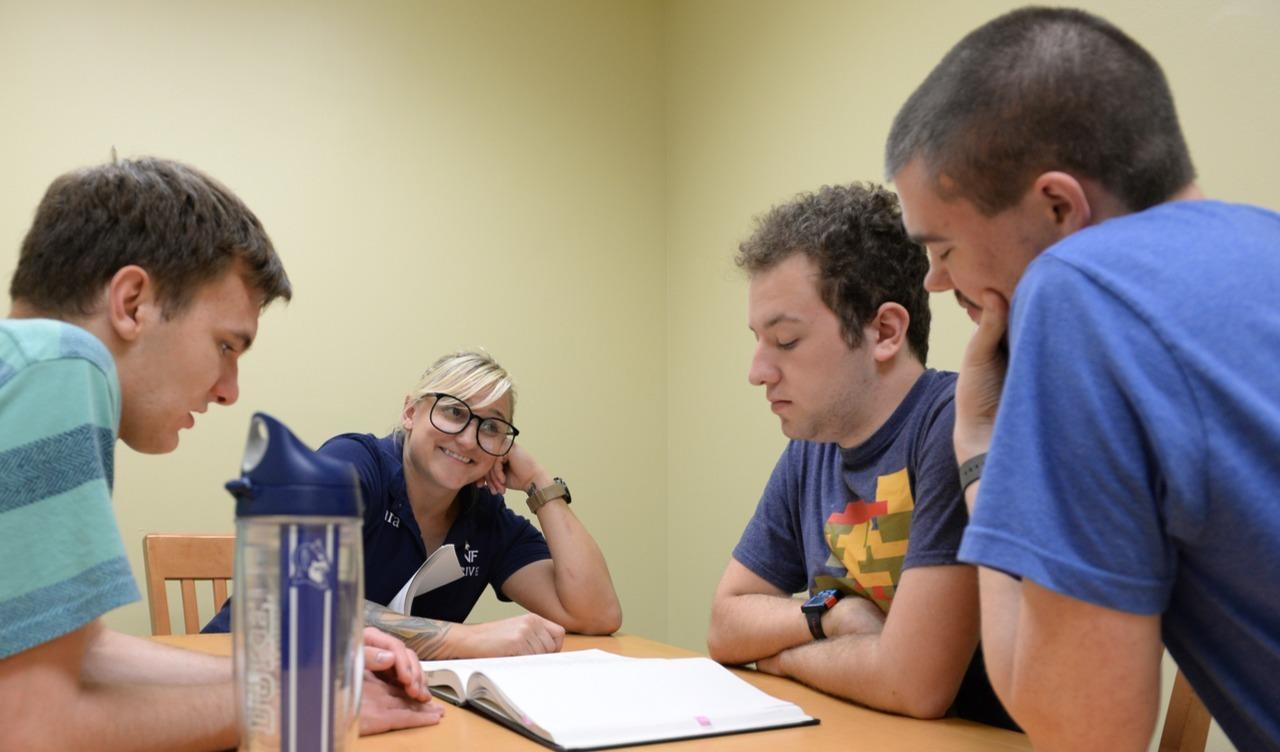 Group of three students and Dr. Tara Rowe reading a book