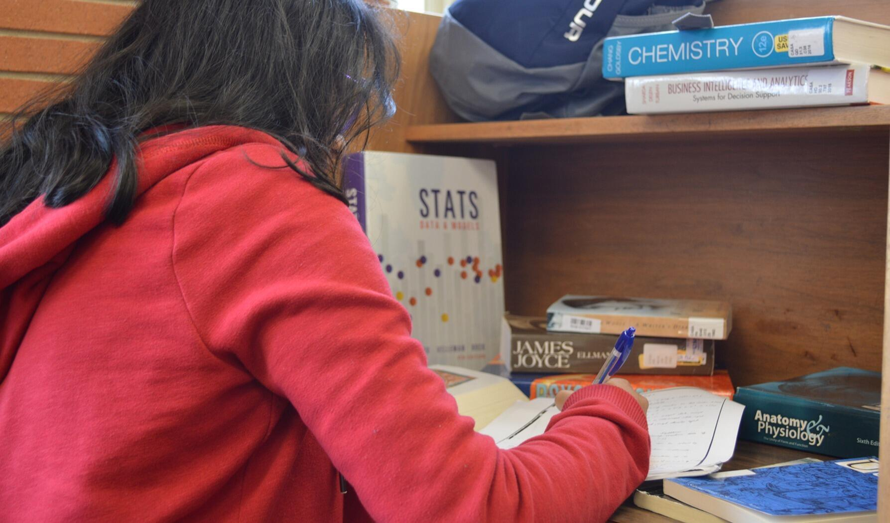 Student studying with textbooks at a desk in a residence hall
